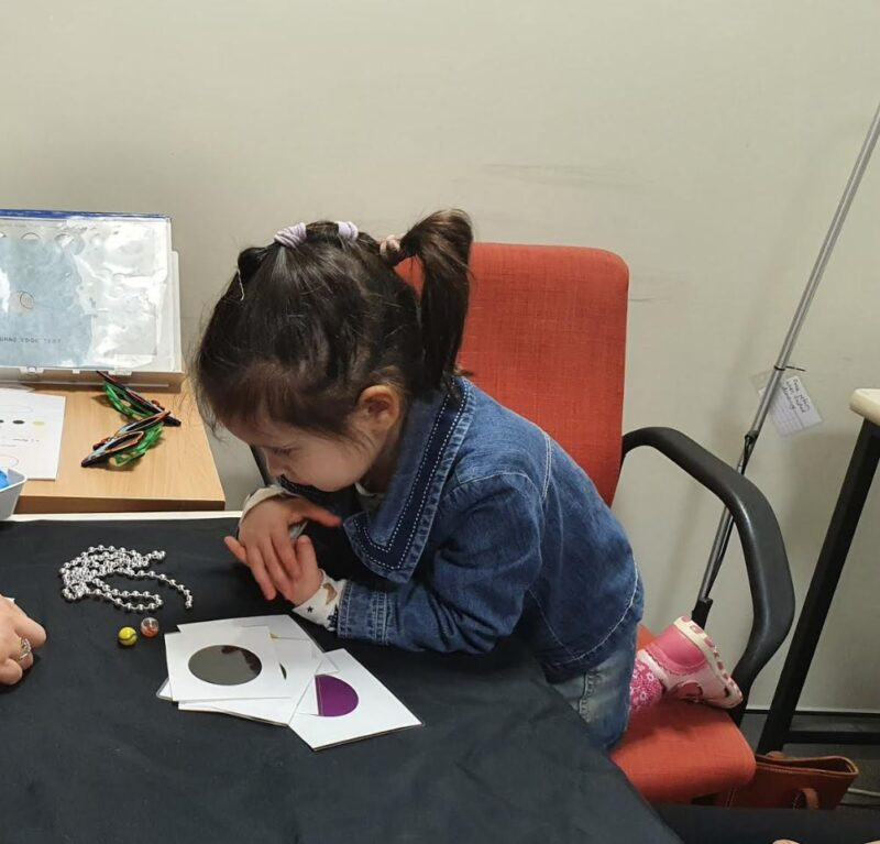 Anna looks at some small balls and objects including marbles and beadson a black table