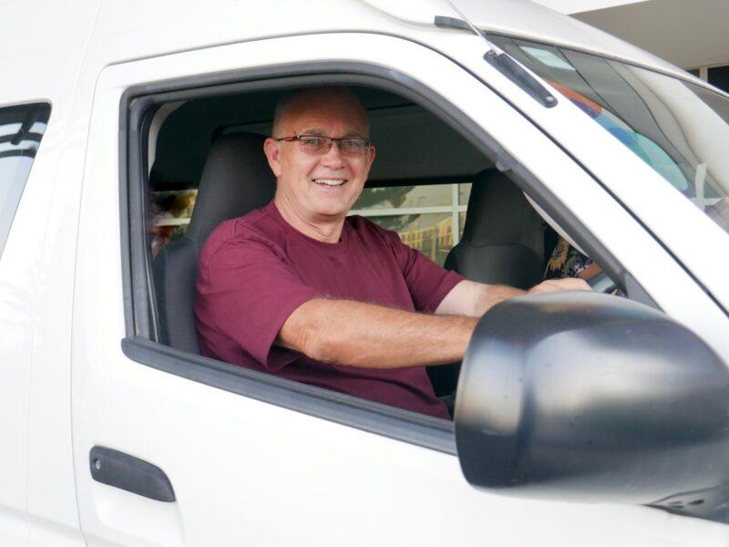 Volunteer driver Graeme sat at the steering wheel of the mini-bus smiling