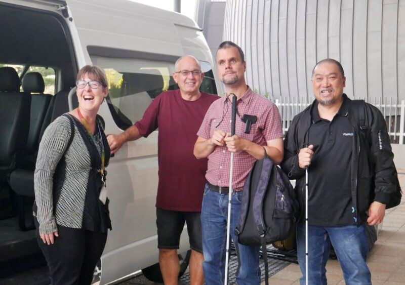 Graeme stands next to the mini bus with Grand Delusion band members