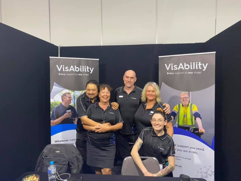 VisAbility's CoAct DES team next to two pull up banners
