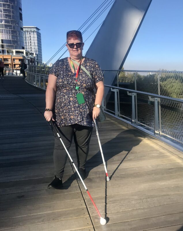 Joanne stands on a bridge holding two canes in her hands