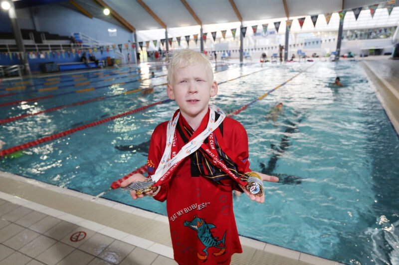 Kaleb in swimming pool holding up his medals