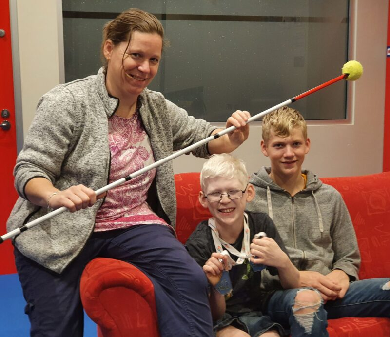 Aafje sets with her two younger children holding teh adapted cane for swimming
