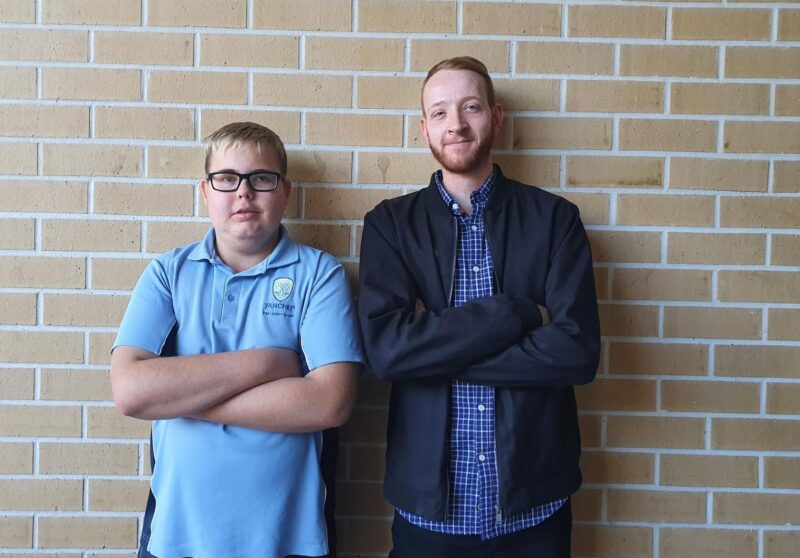 Weiland stands against a brick wall with his English teacher Daniel Castledine