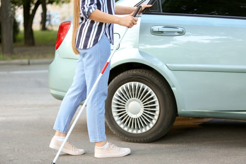 A woman with a white cane opens door of car