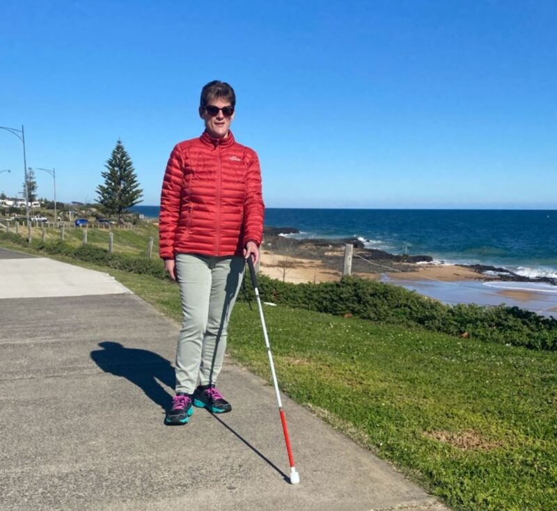 Image shows Nicole with her white cane walking along a footpath close to the sea