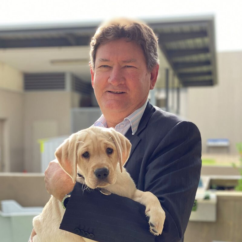 Image shows Tim holding Lucy - a Guide Dog puppy in training