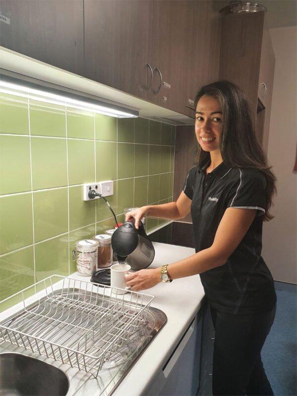 Occupational Therapist Keearny stands next to a kitchen sink pouring water from a kettle