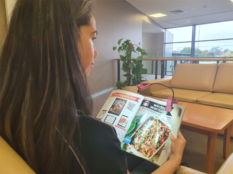 Occupational Therapist Keearny sits reading her magazine. A spotlight throws light onto the magazine page.