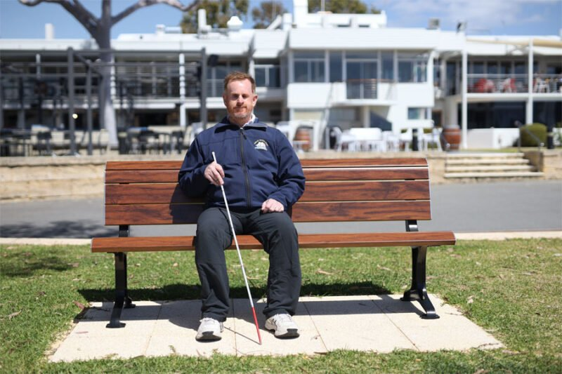 Ryan sits on a bench with his white cane
