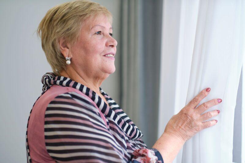 Older woman pulling back blinds