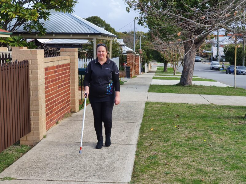 Jodie walks along a path with a support cane