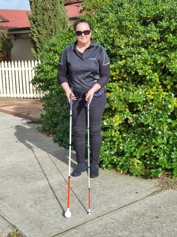 Jodie stands in front of a tree on a path showing the long cane and a fold away cane