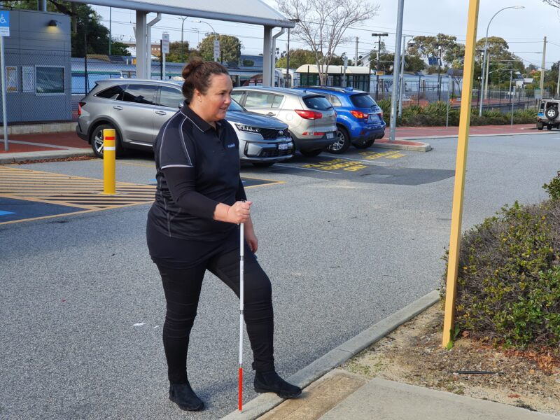 Jodie using a guide cane to step up the kerb at a car park