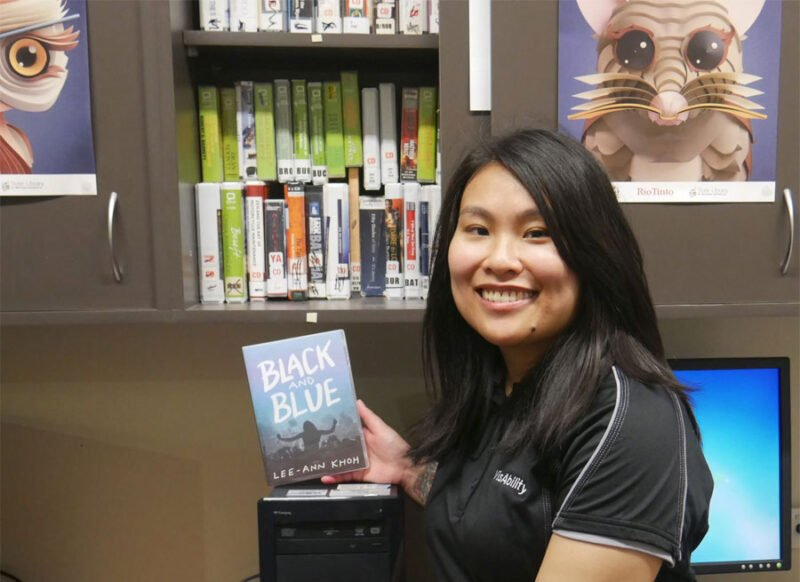 lee-Ann stands in front of the book cupboard in the Audio Library