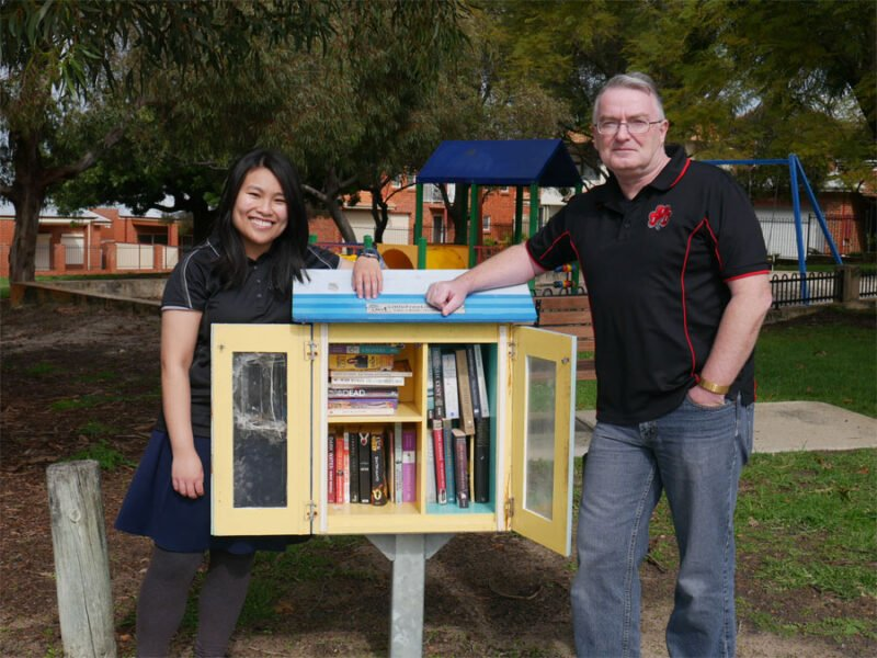 Lee-Ann and her publisher stand next to a book library in Vic Park