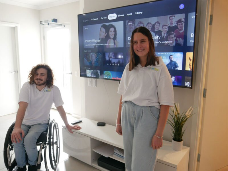 Frank and Christie stand next to a smart television