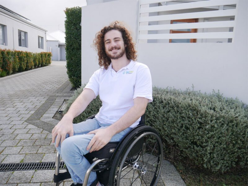 Frank sits in his wheelchair on driveway in front of a house