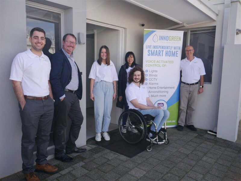 Six staff memebers of Innogreen Technologies stand next to a banner in front of a home