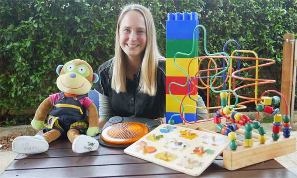 Therapist Emily sits at a wooden table with toys in front of her