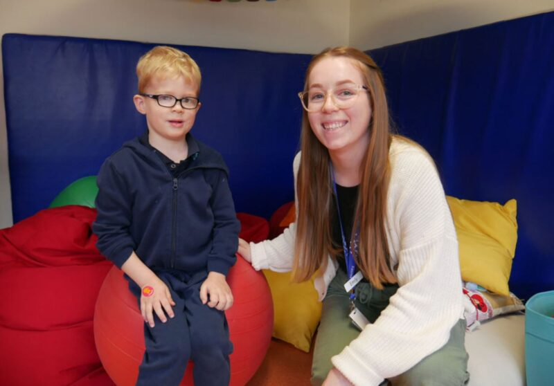 Speech Pathologist Emily crouching next to Harlen in play area filled with bean bags ec