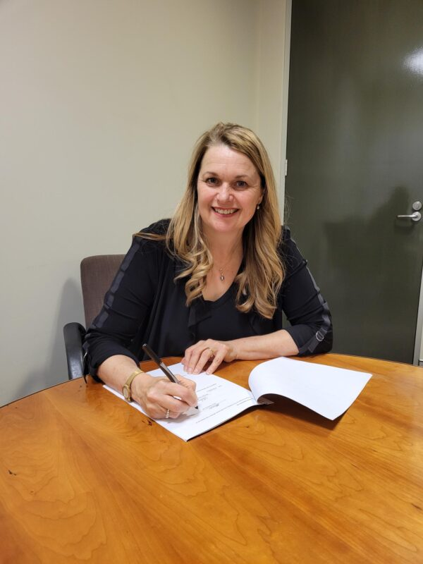 Our CEO signs the State Library partnership. She's seated around a round wooden table.