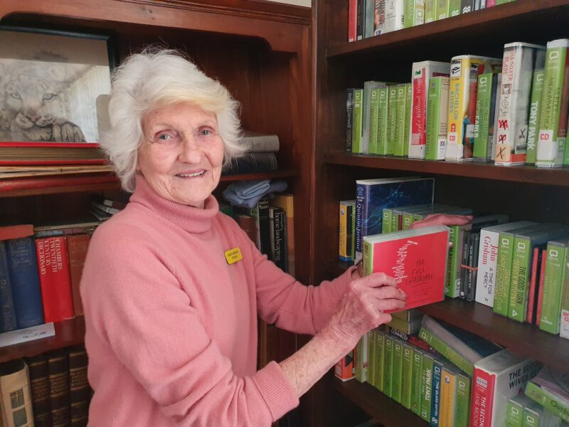 Hilary takes some audio books out of the book shelf