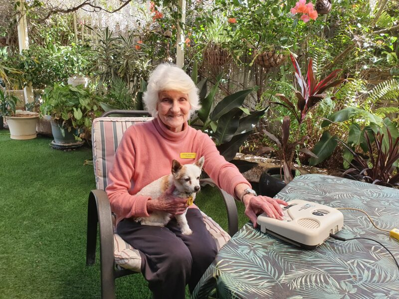 Hilary sits in a garden around a table with dog on her lap and listening to audio books
