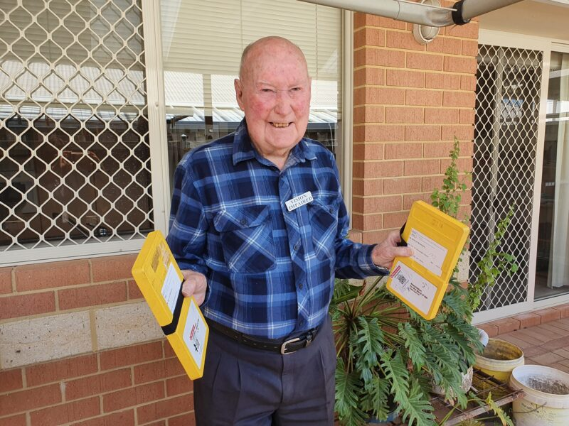 Mervyn stands in his garden with the audio books in each hand