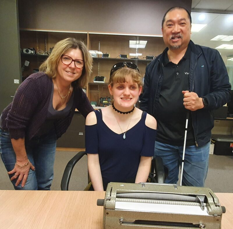 Mel stands next to Tayla and Manny. A Perkins Brailler is on the table in front of them in the assistive technology room.